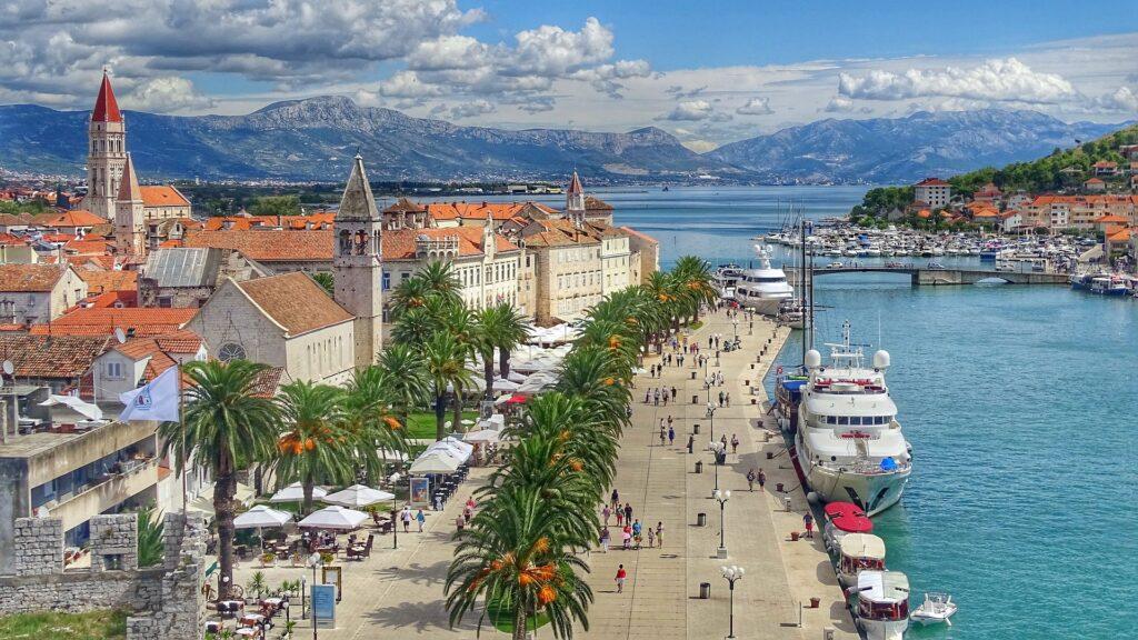 Promenada nadmorska w Trogirze pełna ludzi w sezonie letnim.