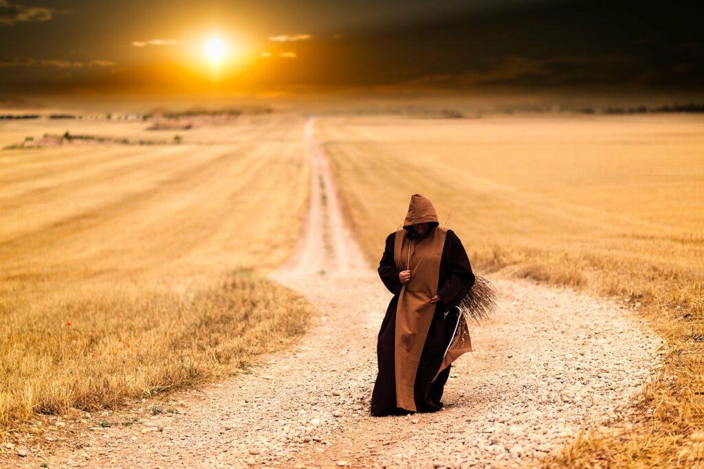 Pielgrzym na szutrowej drodze wśród pól, zachód słońca