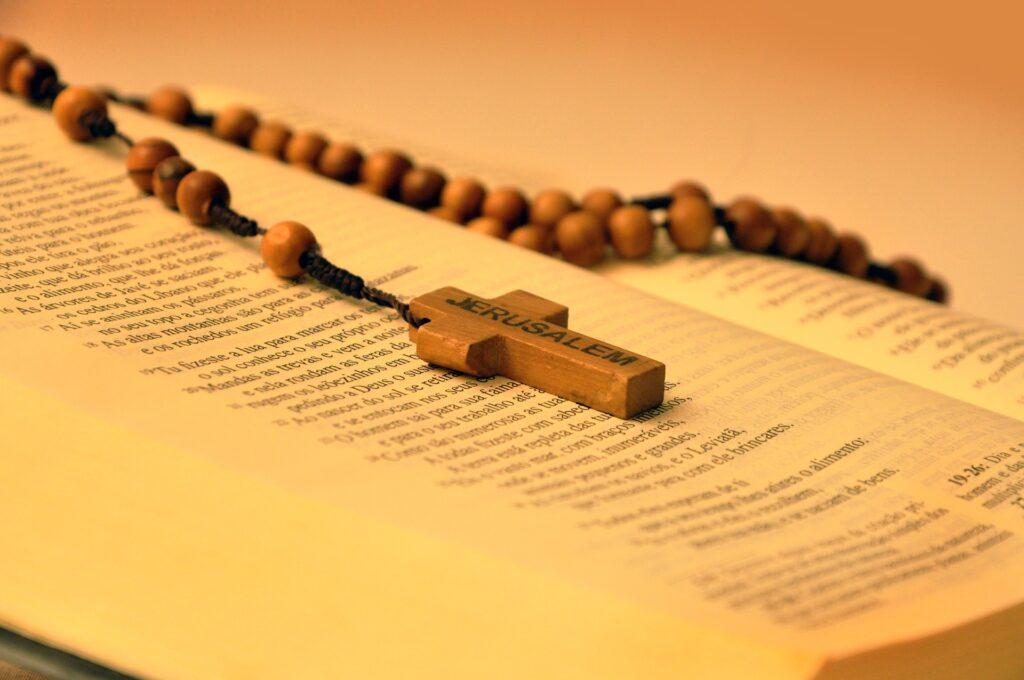 Pamiątki pielgrzymowania - Różaniec z drzewa oliwnego z Jerozolimy leżący na otwartej Biblii.