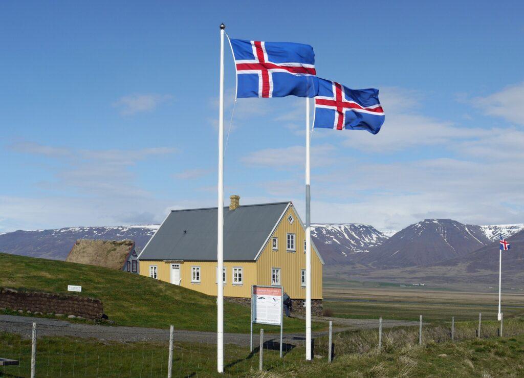 dwie flagi islandzkie na masztach przed budynkiem w islandzkiej wiosce
