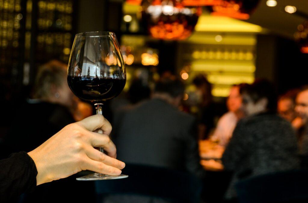 osoba wznosząca toast, trzymająca kieliszek z czerwonym winie na tle biesiadników